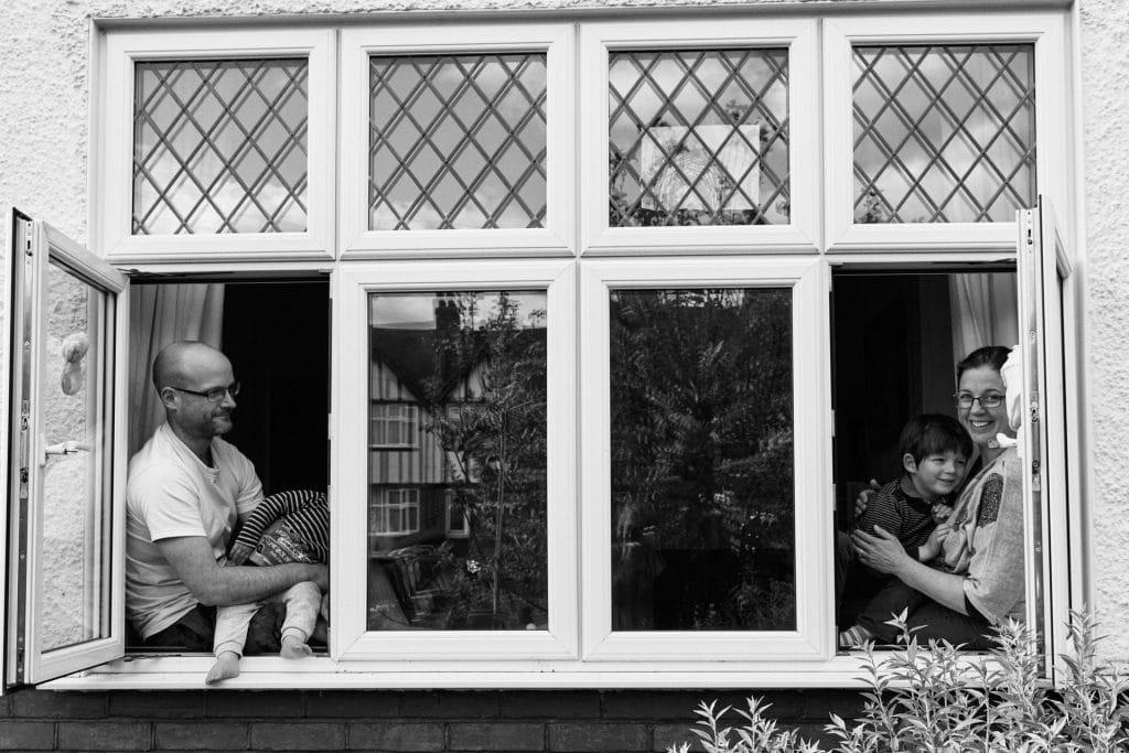 Family sitting in window during corona virus.