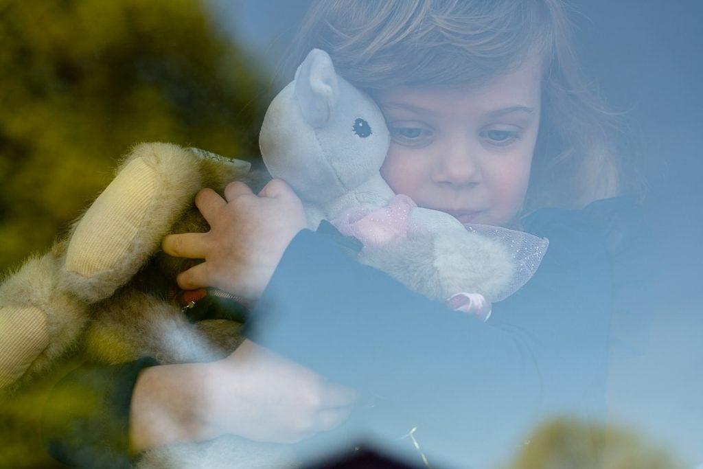 Girl behind window during corona virus pandemic lockdown.