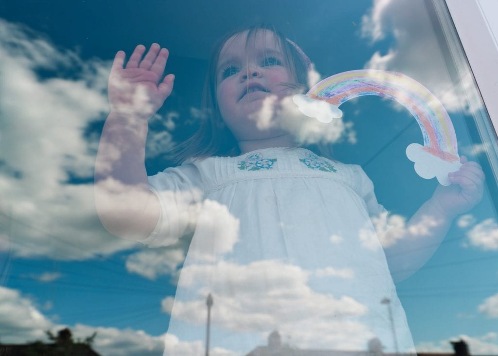 Girl with rainbow behind window during covid-19